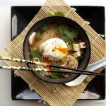 Miso Soup with Poached Egg in a black bowl sitting on bamboo mat sitting on a square black plate.