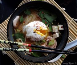 Overhead closeup of Miso Soup with Poached Egg in a black bowl sitting on bamboo mat sitting on a square black plate.