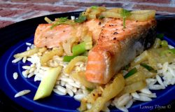 Salmon Steaks with Curried Fennel-Wine Sauce on a bed of white rice sitting on a blue plate.
