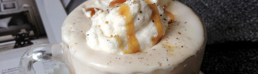 Closeup image of Salted Caramel Ancho Chili Mocha in a mug with whipped cream run down the side. The mug is sitting on a small plate on top of a catalog an grey blanket.