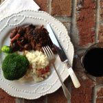 Slow Braised Beef Pot Roast with mashed potatoes and broccoli sitting on white plate on brick background. There's a glass of wine and fork and knife.