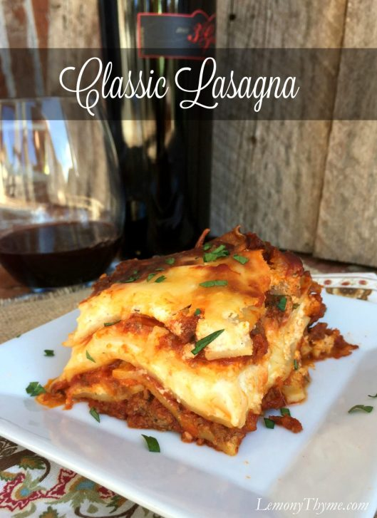 A slice of Classic Lasagna on a white plate with a glass of red wine in the background.