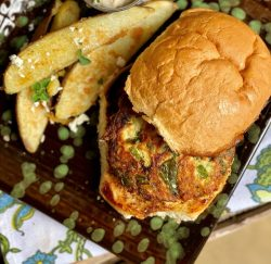 Overhead shot of a Greek Chicken Burger with Greek Style Potato Wedges.