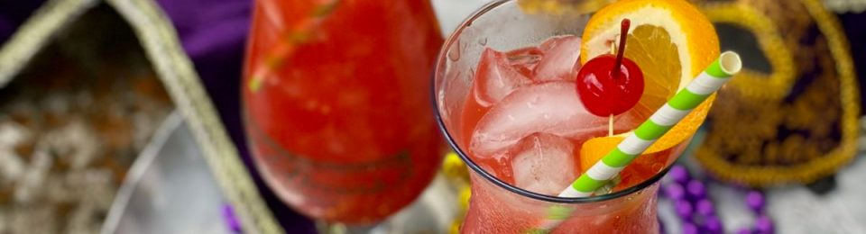 A Hurricane Cocktail is combination of light and dark rums, passion fruit juice, orange juice, squeeze of lime, and grenadine syrup is served over ice in a tall 'Hurricane' glass.
