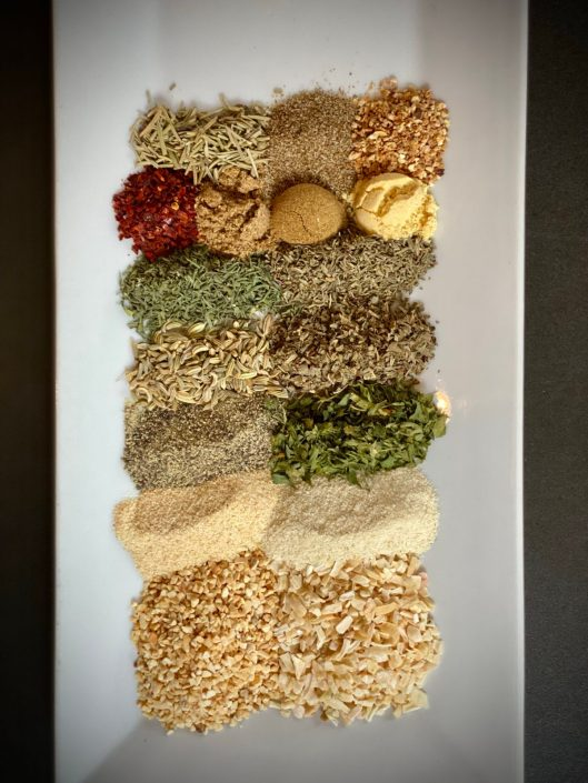 White plate with a variety of ground spices and herbs measured out.