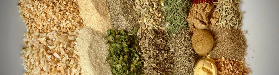 A horizontal image of a variety of spices on a white plate.