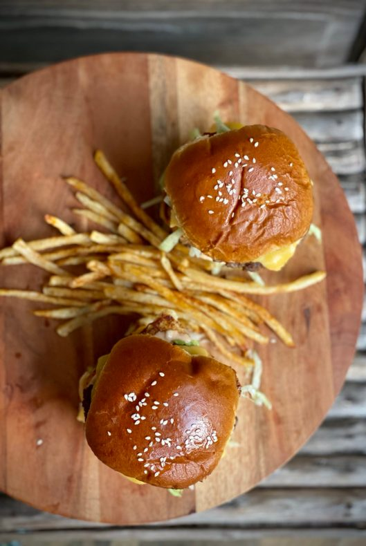 Overhead view of two hamburger buns with french fries sitting on a wooden cutting board