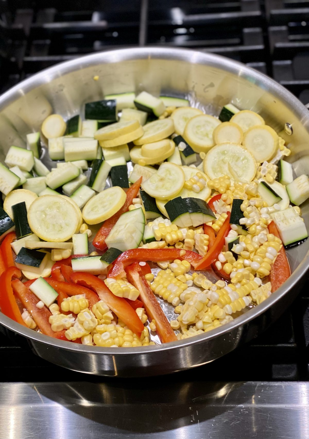 Large skillet with various diced summer veggies