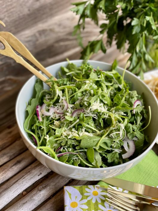 Beautiful Baby Arugula Salad with Lemon Parmesan Vinaigrette in a white bowl sitting on a wooden table.