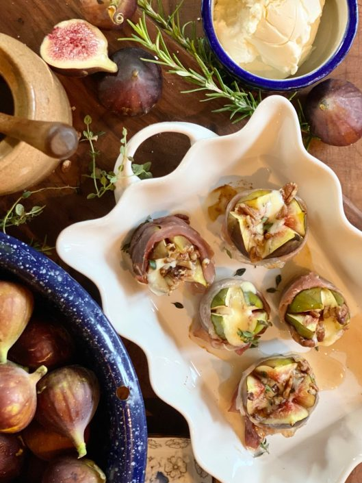 Five prosciutto wrapped stuffed figs in a white baking dish on a wooden table