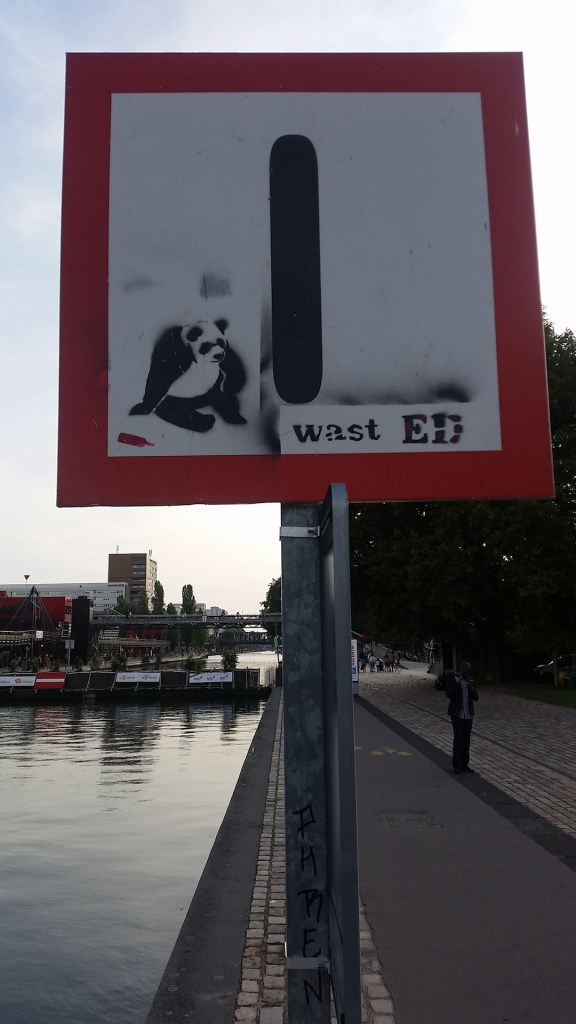 A street sign with graffiti of a panda bear and discarded bottles signed wast ED