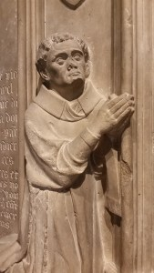 a bas relief of a monk on his knees, praying.