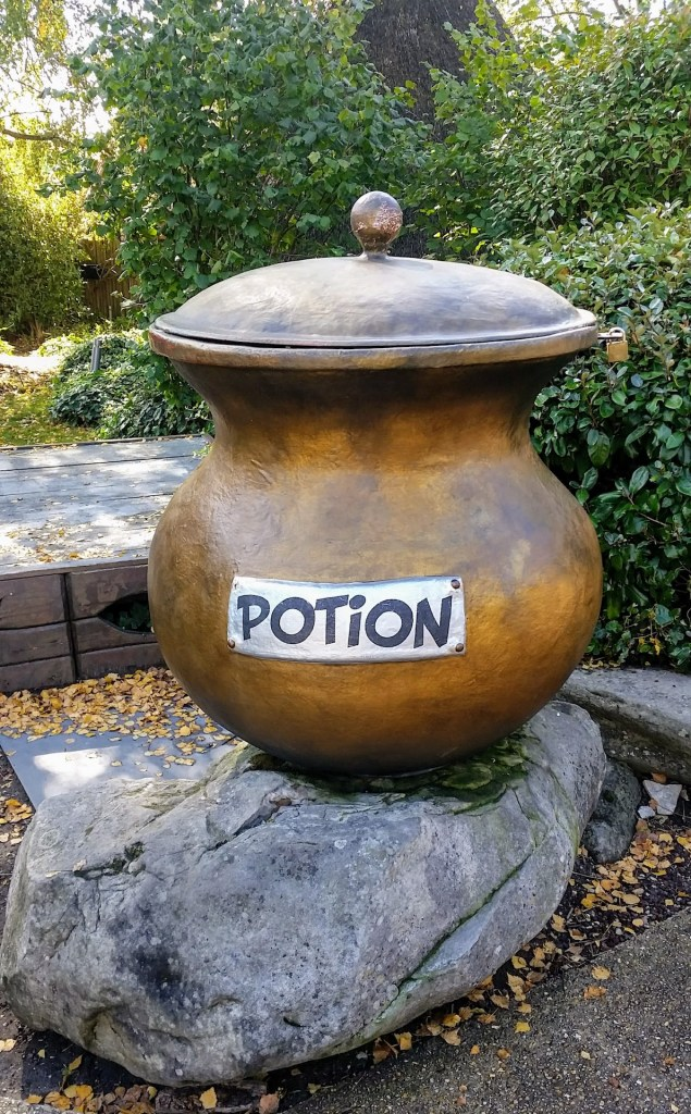 "A big cauldron with a sign saying ""potion"""