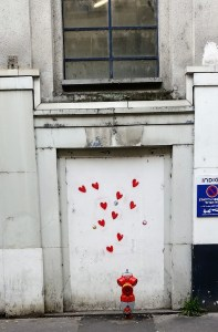 Little red hearts painted on the wall that look like they are rising up from the ground. A little red fire hydrant in the foreground.
