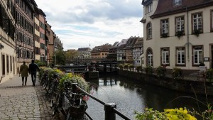 The canal in the middle, with half timbered houses on either side. A couple walking the cobbled streets, holding hands