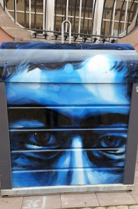 A rubbish bin with a blueish face painted on it.