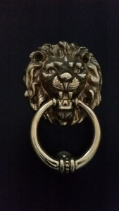 a door knocker in the shape of a lion holding a ring in his mouth