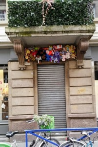 A house entrance with dozens of stuffed toys above the entrance