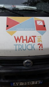 Front of foodtruck witht he slogan What the Truck?! in red, yellow and blue