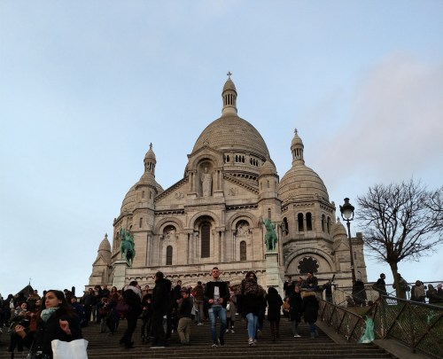 Sacre Cœur, photographed from below with a lot of people on the stairs in the foreground