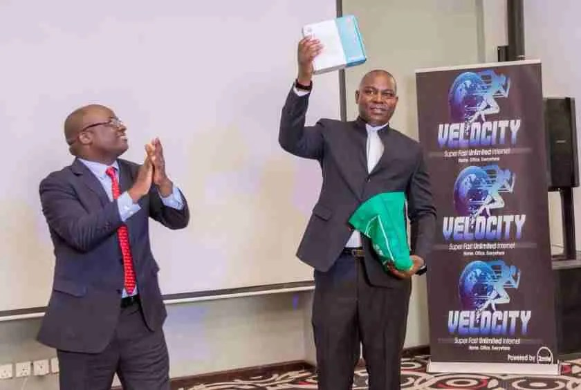 Transport and Comunications Minister Mutotwe Kafwaya displays a Router given to him as a gift at the launch of Velocity as Zamtel CEO Sydney Mupeta cheers on