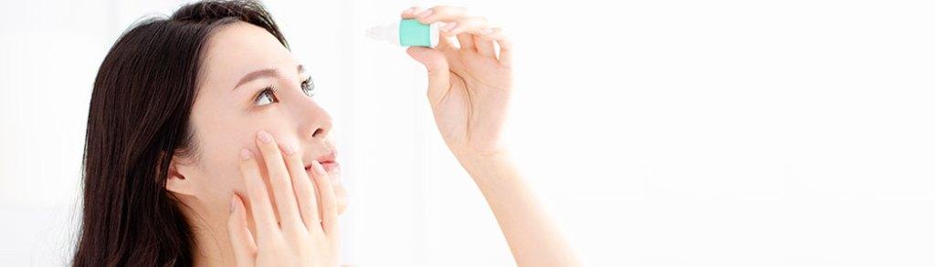 Mulher aplicando colírio