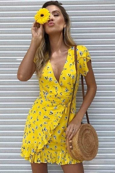 Mulher com vestido amarelo e girassol na mão