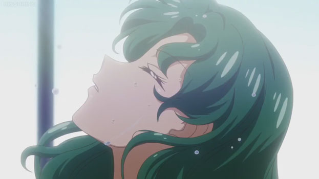 A green-haired woman (Michiru) emerging from the water. All we see is her face as she tilts it back.