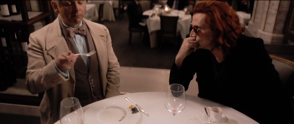 Crowley (Tennant) staring intently at Aziraphale (Sheen) across a table in a fancy restaurant. Aziraphale is happily eating, while Crowley is wearing shades indoors.