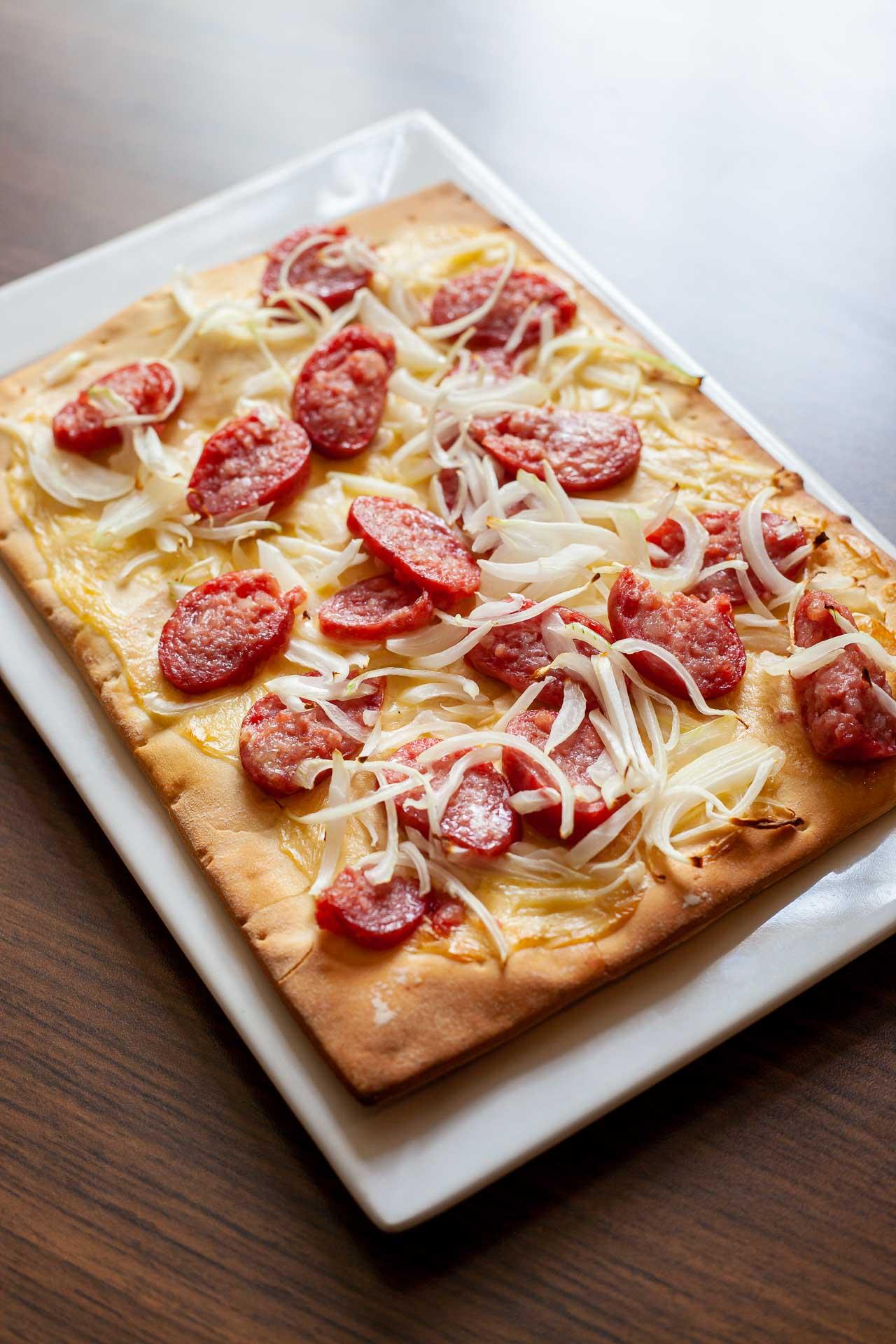 Flammkuchen, a tradicional pizza alemã, em formato quadrado, com cebolas e linguiça blumenau