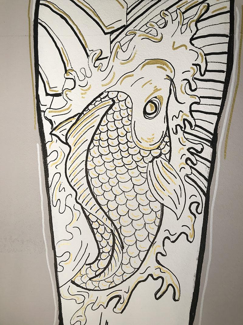 Disegno di una carpa tatuata su un braccio
