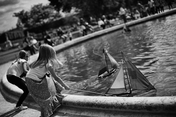 GIrls playing with tiny little wooden boats in Tuileries garden