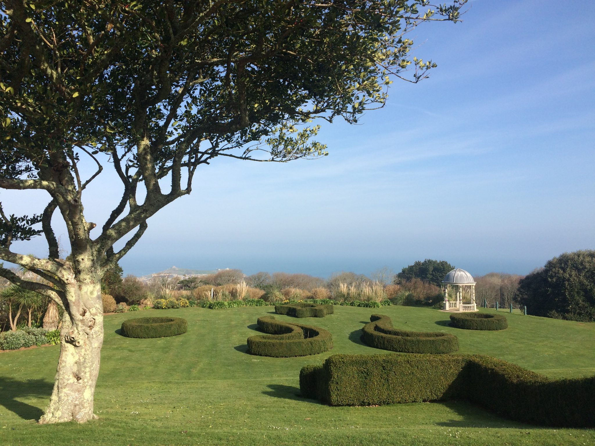 Tregenna castle gardens with a blure sky and lush green hedges and grass