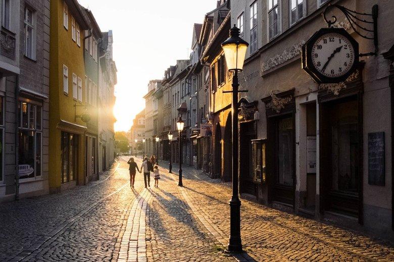 famille se promenant dans une rue pavée au soleil couchant