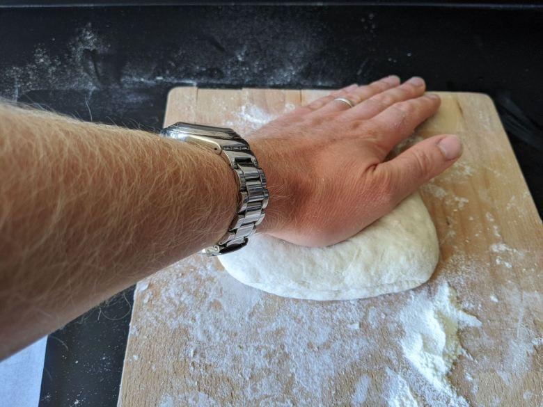 main qui applatit un paton de pain