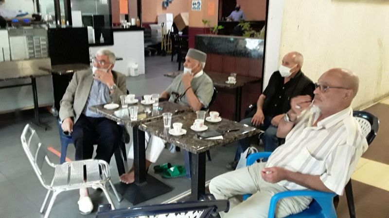"""In front of Asian fast food, these retirees spend the afternoon chatting over coffee.  """"We don't really know what we're going to do now,"""" worries Mohamed (right).  LP / F.-XR"""