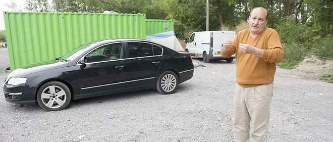 Le maire de Téteghem, Frank Dhersin, dans le camp de migrants, à côté d'une berline immatriculée en Grande-Bretagne.