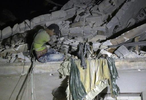 Un adolescent syrien attend d'être secouru dans les ruines d'un immeuble après un raid aérien à Alep, le 16 octobre 2016 © THAER MOHAMMED AFP