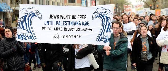 """Réunis devant le centre de convention de Washington, des manifestants brandissent une pancarte : """"Les juifs ne seront pas libres tant que les Palestiniens ne le seront pas. Rejetez l'AIPAC, rejetez l'occupation."""""""