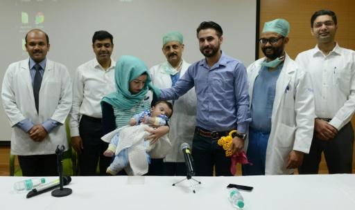 Les parents irakiens Gufran Ali (3e à gauche) et Sarwed Ahmed Nadar (3e à droite) avec leur bébé de huit mois et les médecins, le 14 avril 2017 près de New Delhi © Money SHARMA AFP