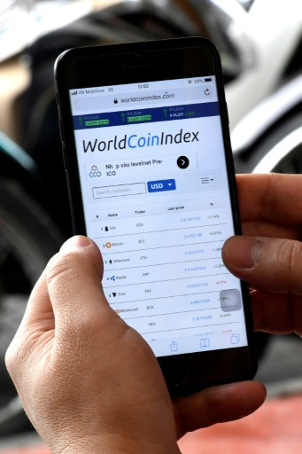 "Photo d'un investisseur vietnamien dans les cryptomonnaies qui surveille l'indice ""world coin index"" sur son smartphone à Hanoi le 12 avril 2018 © Nhac NGUYEN AFP/Archives"