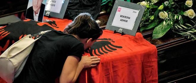 Des proches s'inclinent devant les cercueils des victimes.Ici les deux victimes albanaises recouvert du drapeau de leur pays. Un moment dedie leur a ete copnsacre pendant la ceremonie des funerailles, declenchant les applaudissements de l'assistance.