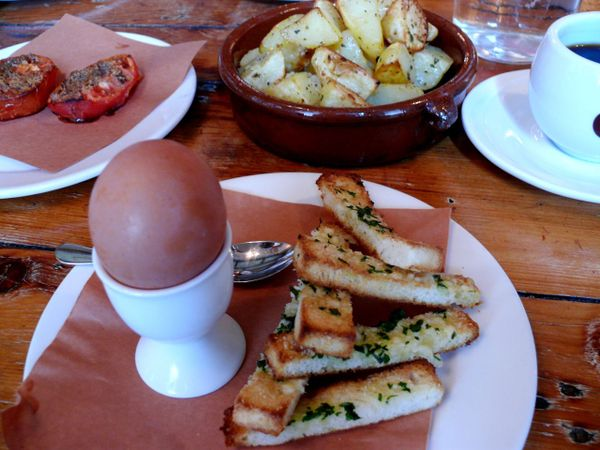 soft boiled egg with parmesan shoes, roast potatoes and tomatoes