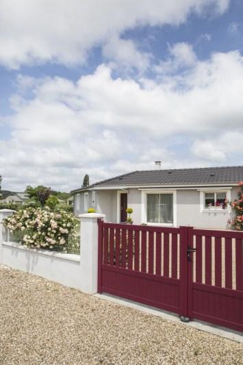 Maison de plain-pied vue de l''extérieur avec un portail rouge