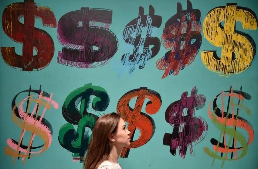 Un'impiegata passa davanti a un lavoro della serie Dollar signs di Andy Warhol esposta da Sotheby's, a Londra.