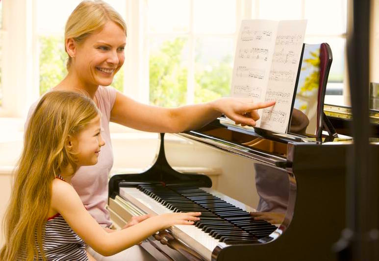 Piano Teacher and Girl sitting at piano lesson
