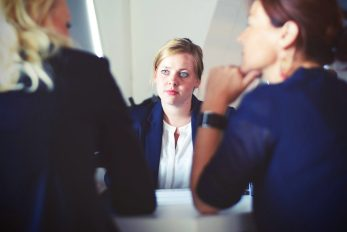 """A woman in an interview being asked """"Do you have any questions for us?"""" (Photo by Tim Gouw from pexels.com)"""