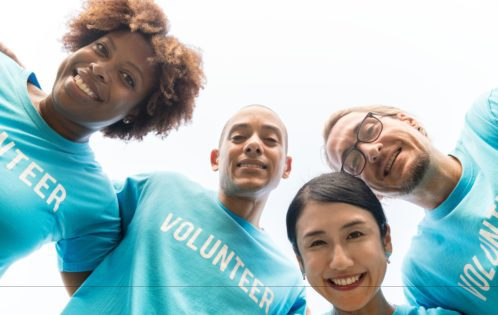 """A group of four young adults wearing blue t-shirts that say """"VOLUNTEER."""""""