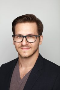 A headshot of a smiling man in glasses and a sportcoat – an example of good attire for a LinkedIn headshot.