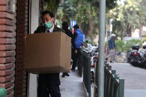 A man wearing a mask carries a package through a door. Photo by Macau Photo Agency on Envato Elements.